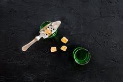 Traditioner av att dricka absint Speciala sked- och sockerkuber nära skott på svart utrymme för kopia för bästa sikt för bakgrund Royaltyfria Bilder