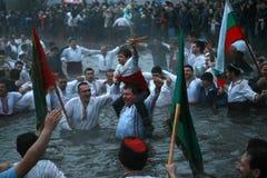 Traditions d'épiphanie - Jordanie Les hommes dansent dans les eaux glaciales de la rivière Tunja le 6 janvier 2011, Kalofer, Bulg Photos stock