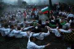 Traditions d'épiphanie - Jordanie Les hommes dansent dans les eaux glaciales de la rivière Tunja le 6 janvier 2011, Kalofer, Bulg Image stock