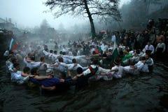 Traditions d'épiphanie - Jordanie Les hommes dansent dans les eaux glaciales de la rivière Tunja le 6 janvier 2011, Kalofer, Bulg Images libres de droits