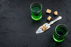 Traditions of drinking absinthe. Special spoon and sugar cubes near shots on black background top view copy space. Traditions of drinking absinthe. Special spoon Stock Image
