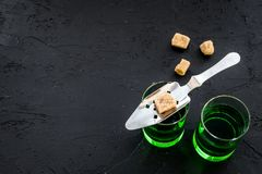 Traditions of drinking absinthe. Special spoon and sugar cubes near shots on black background top view copy space. Traditions of drinking absinthe. Special spoon Stock Photography
