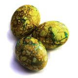 Handmade yellow green easter eggs painted marbled over white background royalty free stock photo