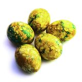 Handmade yellow green easter eggs painted marbled over white background stock image