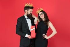 Traditions royales Célébrez l'anniversaire Cadeau royal Roi dans la couronne d'or de smoking donnant le boîte-cadeau à la reine d images stock