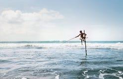 ` Tradizionale del bastone del ` della Sri Lanka - il pescatore di cattura del pesce di metodo nell'Oceano Indiano ondeggia fotografia stock libera da diritti