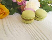 Tradizionale francese colorato del macaron dolce è aumentato su un fondo di legno bianco, francese di alstroemeria Immagine Stock