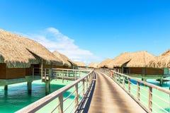 Tradizionale sopra le ville dell'acqua su una laguna tropicale di Bora Bora Fotografia Stock