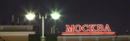 Tradução do russo da inscrição: Moscou Texto de néon da iluminação contra o céu Imagens de Stock Royalty Free