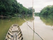 Tradycyjna łódź jest w lokalnym kanale otaczającym naturalnymi roślina lasami Zdjęcie Royalty Free