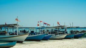 Tradycyjna łódź z Indonezja flaga wykładającą w górę z rzędu zakotwiczający w dennego brzeg plaży zdjęcia stock