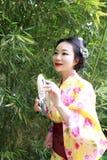 Tradycyjna Azjatycka Japońska kobieta z kimonem z fan na ręce stał bezczynnie bambusa w wiosna parku Fotografia Stock