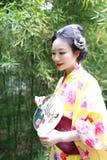 Tradycyjna Azjatycka Japońska kobieta z kimonem z fan na ręce stał bezczynnie bambusa w wiosna parku Obraz Stock
