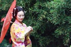 Tradycyjna Azjatycka Japońska panna młoda z kimonowym chwytem czerwony parasol stał bezczynnie bambusa w parku Zdjęcie Stock