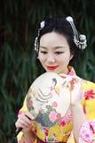 Tradycyjna Azjatycka Japońska piękna kobieta z fan na ręce stał bezczynnie bambusa w ogródzie Zdjęcia Stock