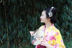 Tradycyjna Azjatycka Japońska piękna kobieta z fan na ręce stał bezczynnie bambusa w ogródzie Zdjęcia Royalty Free