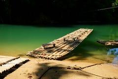 Tradycyjna bambusowa tratwa unosi się nad jasną rzeką w ranku Obrazy Royalty Free