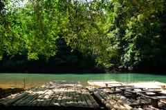 Tradycyjna bambusowa tratwa unosi się nad jasną rzeką w ranku Zdjęcia Royalty Free