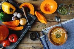 Tradycyjna domowej roboty dyniowa polewka z seads, śmietanką i warzywami na nieociosanym drewnianym stole, Fotografia Royalty Free