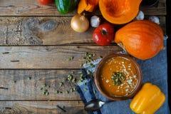 Tradycyjna domowej roboty dyniowa polewka z seads, śmietanką i warzywami na nieociosanym drewnianym stole, Zdjęcie Royalty Free