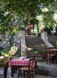 Tradycyjna Grecka tawerna z drewnianym stołem i krzesłami lokalizować pod zielonymi drzewami na Crete wyspie, Grecja fotografia stock