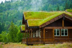 Tradycyjna norweska drewniana domowa pozycja na gazonie i górach w tle typowy domowy norweg typowy norweg zdjęcia royalty free