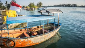 Tradycyjna stara łódź na brzeg błękitnej wodzie morskiej z zieloną wyspą w odległości w karimun jawie obrazy stock