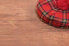 Tradycyjna Szkocka Czerwona tartan czapeczka na drewno desce obraz stock