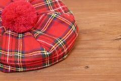 Tradycyjna Szkocka Czerwona tartan czapeczka na drewno desce zdjęcia royalty free