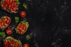 Tradycyjna w?oszczyzna Bruschetta z pomidorami, mozzarella kumberlandem, sa?atka li??mi i baleronem na ciemnym batuty tle siekaj? zdjęcia royalty free