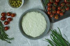 Tradycyjna w?oszczyzna Focaccia z pomidorami, oliwkami i rozmarynami, Focaccia kulinarny proces, sk?adniki Focaccia ciasto zdjęcie stock