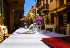 Tradycyjne Grecja serie - ulicznych tavernas biały tablecloth na stole na tle stare ulicy, głębia fotografia stock
