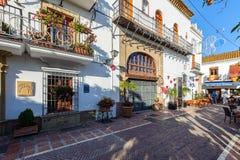 Tradycyjne hiszpańszczyzny zwężają się ulicę z pamiątkarskim sklepem i piękną architekturę w dziejowej części miasteczko Obraz Royalty Free