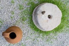 Tradycyjnego kamienia Młyński i Gliniany garnek w ogródzie zdjęcie royalty free