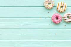 Tradycyjni ameryka?scy donuts r??ni smaki na mennicy zieleni t?a drewnianym mieszkaniu k?a?? mockup zdjęcie stock
