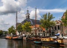 Tradycyjni drewniani żeglowanie statki w wodnym kanale Kościół na tle Stary historyczny schronienie Schiedam obraz royalty free