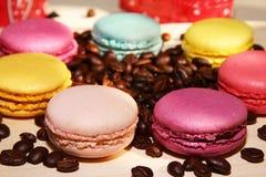 Tradycyjni francuscy kolorowi macarons z kawowymi fasolami na drewnianym tle Zdjęcie Royalty Free