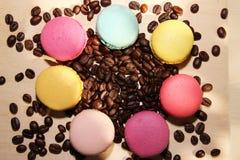 Tradycyjni francuscy kolorowi macarons z kawowymi fasolami na drewnianym tle Zdjęcia Stock
