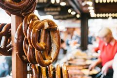 Tradycyjni precle dzwonili Brezel zrozumienie na stojaku przeciw tłu zamazany uliczny rynek i ludzie dalej Obraz Stock