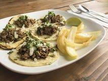 Tradycyjni przypadkowi Meksykańscy foods piec na grillu wołowiien fajitas tacos jedzą lunch lub obiadowy posiłek na białym cerami Obrazy Stock