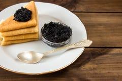 Tradycyjni rosyjscy bliny na talerzu z czarnym kawiorem Zdjęcia Royalty Free