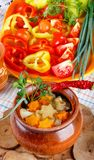 Tradycyjni wieśniaka domu gulyas z surowymi warzywami i pikantność w glinianych garnkach na drewnianym stole, obraz stock
