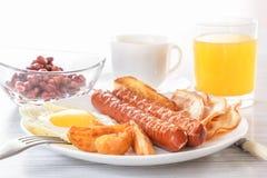 Tradycyjny Angielski śniadanie - smażący jajko na pogodnej stronie, kiełbasy, fasole Szkło świeży sok Filiżanka herbata z mlekiem Obrazy Royalty Free