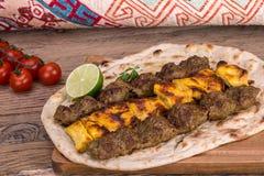 Tradycyjny Bliskowschodni Perski kurczaka i baranka mięsny szaszłyk Kebab skewered mięsa BBQ grilla na płaskim pita chlebowym i s Zdjęcie Royalty Free