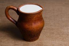 Tradycyjny dzbanek wypełniał z odżywczym świeżym mlekiem na drewnianym stole obrazy stock