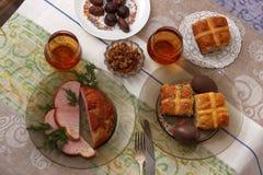 Tradycyjny Easter obiadowy ustawiający z pokrojonym mięsem, chlebem z ziele, handmade barwionymi jajkami, czekoladami, Easter tor Fotografia Royalty Free