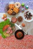 Tradycyjny Easter obiadowy ustawiający z pokrojonym mięsem z cytryną i ziele, chleb, handmade barwioni jajka, czekolady, rodzynki Zdjęcie Stock