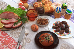 Tradycyjny Easter obiadowy ustawiający z pokrojonym mięsem z cytryną i ziele, chleb, handmade barwioni jajka, czekolady, rodzynki Obrazy Stock