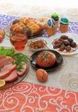 Tradycyjny Easter obiadowy ustawiający z pokrojonym mięsem z cytryną i ziele, chleb, handmade barwioni jajka, czekolady, rodzynki Zdjęcia Royalty Free