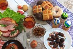 Tradycyjny Easter obiadowy ustawiający z pokrojonym mięsem z cytryną i ziele, chleb, handmade barwioni jajka, czekolady, rodzynki Zdjęcie Royalty Free
